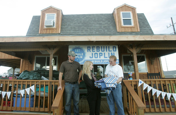 Globe/Roger Nomer<br /> Brad Mudge and Tara Clark, from Rebuild Joplin, present a quilt made by volunteers to Mike John at his rebuilt house on Byers on Friday evening.