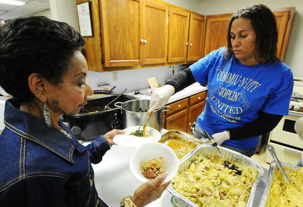 Globe/T. Rob Brown<br /> One of the winners of the Soul Food Cookoff, Janice Booth, who took first-place side dish for her collard greens, is served some of her own greens by Tabitha Smith of Joplin.