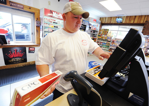 Globe/T. Rob Brown<br /> Braxton Perry, Cigs & Suds salesman, rings up a customer's drive-through cigarette purchase Monday morning at the Webb City business.