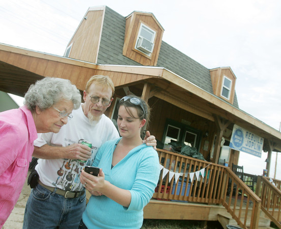 Globe/Roger Nomer<br /> Betty John, John's mother, left, Mike John and Hannah Nally, John's daughter, look a photos in front of his rebuilt house on Byers on Friday evening.