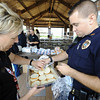 Globe/T. Rob Brown<br /> Pittsburg, Kan., Police Chief Mendy Hulvey, left, and acting Sgt. Chris Moore prepare hamburger buns to receive freshly grilled burgers during the Badges & Burgers annual fall fundraiser event for the United Way on Wednesday afternoon, Oct. 17, 2012. Both the Pittsburg Fire and Police departments were involved in preparing and serving the food and beverages.