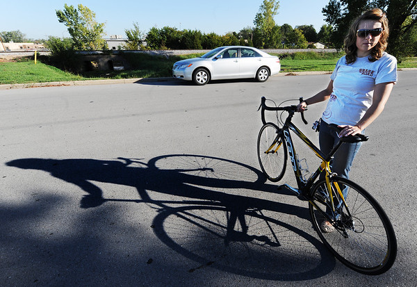 Globe/T. Rob Brown<br /> Ruth Sawkins, of Joplin, who is a member of the Look campaign and its Share the Road program, which hopes to cast a reminder on the minds of motorists to be more aware of bicyclists, runners and walkers, casts her bicycling shadow on the road Wednesday morning, Oct. 3, 2012, near the intersection of Murphy Boulevard and Campbell Parkway.