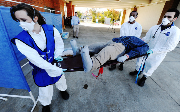Globe/T. Rob Brown<br /> Karen Watts, left, infection prevention officer with Freeman Health System and treatment area supervisor, and two Labette Community College students, Felix Karuga, center, nursing student, and Drew Patton, paramedic student, carry a dummy during a decontamination exercise at Freeman West Tuesday morning, Oct. 16, 2012.