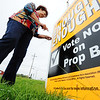 Globe/T. Rob Brown<br /> Earlene Jimerson, of Joplin, a sales representative with Excalibur International, a cigarette manufacturer, puts up a sign of opposition to Proposition B Monday morning in front of Cigs & Suds, on Madison in Webb City.