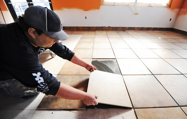 Globe/T. Rob Brown<br /> Ronnie Lanie, a tile setter with Cal Construction of Kansas City, Mo., works on the interior of the nearly rebuilt Taco Bell on South Main Street Thursday afternoon, Oct. 18, 2012, in Joplin.