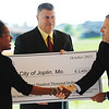 Globe/T. Rob Brown<br /> Joplin Mayor Melodee Colbert-Kean, left, shakes hands with Carl Brooks, EPA Region 7 administrator, as Joplin City Manager Mark Rohr holds a check for $2.4 million presented Thursday morning, Oct. 4, 2012, from the EPA to the city of Joplin at Parr Hill Park.
