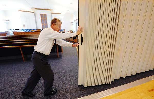 Globe/T. Rob Brown<br /> Creed Jones, Stake president in Joplin, opens up a divider between the sanctuary and the multipurpose room, one of many improvements inside the rebuilt Church of Jesus Christ of Latter Day Saints (LDS) Monday afternoon, Oct. 15, 2012. The Joplin church, located across the street from Joplin High School, was destroyed during the May 22, 2011, tornado.