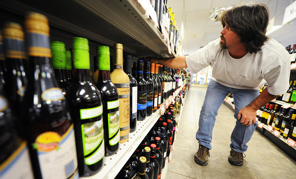 Globe/T. Rob Brown<br /> Jason Wood, cashier for The Jug Store Liquors, arranges the store's shelves of alcohol Tuesday afternoon, Oct. 9, 2012, at the convenience and liquor store located just north of the Arkansas border on 71 Highway.