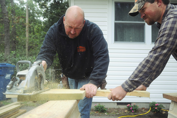 Globe/Roger Nomer<br /> Tim Story, left, and Shaun McConnaughey, both from Neosho, cut a board for a porch at 115 N. Patterson during Saturday's Hearts and Hammers event.