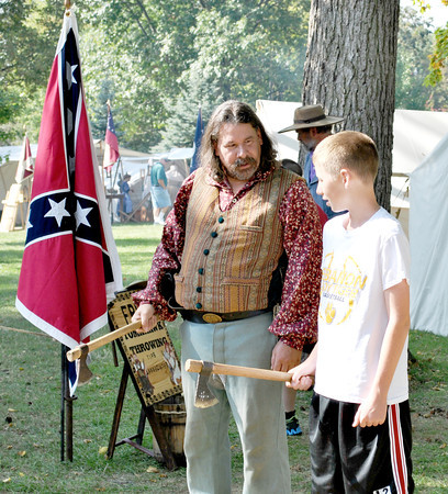 "Photo by Morgan Rowe/For The Lebanon Reporter<br /> Sam Hood, 14, tries his hand at throwing a tomahawk Saturday at the Lincoln's Lebanon and Civil War Re-enactment hosted by the Boone County Historical Society Saturday and Sunday. ""It was a very cool experience, I have never one before."""