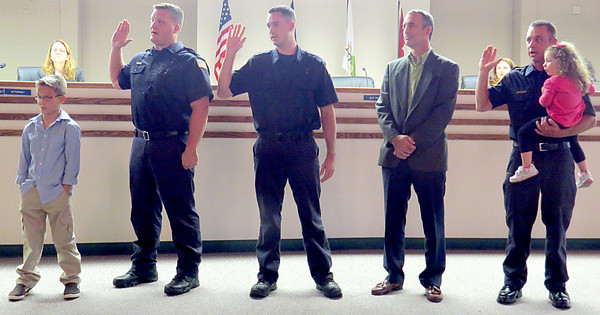 Zionsville firefighters Dennis Eckert, Evan Maher and Sean Mitchel are sworn into office during the Zionsville Town Council meeting Monday night, Oct. 7. Pictured are Eckert and his son Brenden, Maher and his father John, and Mitchel and his daughter Lexi.