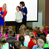 Indiana's 2013 Teacher of the Year Suzanne Whitton reads a plaque before presenting it to Eagle Elementary fourth-grader Ashley Kolman, standing with Indiana First Lady Karen Pence, who was an art teacher for 25 years. Kolman was the only student from Indiana - and the youngest - to have her artwork selected for a calendar promoting awareness of cyber security. Kolman and other Eagle students submitted their artwork last year; Kolman's picture of a person typing at a computer monitor and warning people not to click on pop-ups was selected to move on to the national level. There, it was chosen for the calendar's September artwork. Multi-State-Information Sharing & Analysis Center ( MS-ISAC ) is the sponsoring organization for the Kids Safe Online Poster Contest, in which schools from all 50 states participated. The calendar release and the presentation of Kolman's award coincide with National Cyber Security Awareness Month.