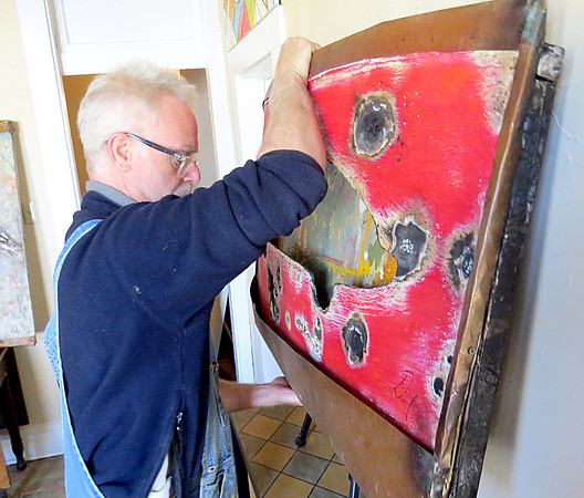 Artist Doug Arnholter places a piece of his work Thursday afternoon, Sept. 26, at his new studio on Main Street.