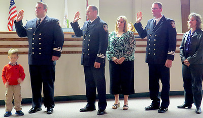 Zionsville firefighters Jason Potts, David Kail and Todd Scales are sworn in as captains during the Zionsville Town Council meeting Monday night, Oct. 7. The three captains were the top scoring applicants after participating in a promotion process consisting of written testing, oral interviews, pratical skills evaluations and physical agility. Pictured are Jason Potts and son Drew, David Kail and his wife Emily, and Todd Scales and his wife LeighAnn Akard.