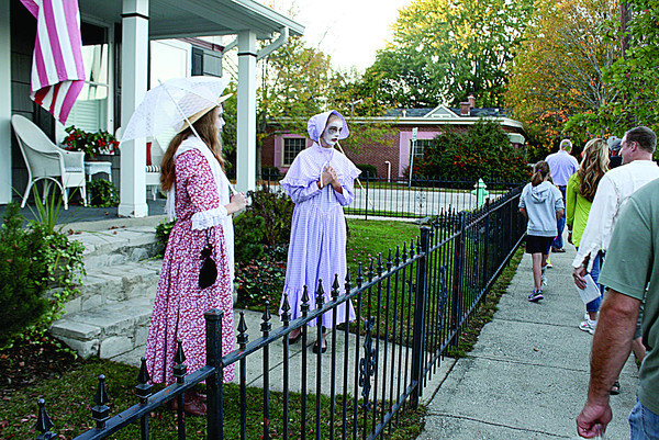 At 210 S. Second St., the ghosts of Mrs. Green, left, played by Sarah Satterfield, and Mrs. Mills, played by Lauren Masoncup, discuss the untimely demise of their neighbor, Mrs. Ross, who died of consumption. Otherwise known as tuberculosis, or TB, consumption took the lives of many people before public health improved and treatment and prevention were available. The short drama was part of the 11th annual Ghost Walk to raise funds for the SullivanMunce Cultural Center. Tour Guide Monty Young told his group all stories on the tour are from actual historical events, although some creative license is taken. Satterfield is a freshman at Zionsville Community High School, and Masoncup is a freshman at University High School.