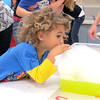 Colin Garringer blows bubbles to create a piece of artwork Friday morning, Sept. 27, at Hussey-Mayfield Memorial Public Library. The four-and-a-half-year-old boy was one of nearly 20 kids that blew bubbles into a mixture of water, soap, and paint to create a piece of artwork. Once the bubbles were high enough, the children were able to place a piece of paper on top to pop the bubbles and paint their paper.