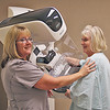 Elizabeth Pearl | The Lebanon Reporter<br /> 3D IMAGE: Denise Barker, left, the lead mammography technologist at Witham's women's health center, demonstrates the new 3D mammogram machine on Terre Drummond, a bone density technician.