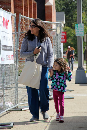CAN'T WAIT: Shazia Baker and daughter Nya, 6, peer into the pocket park construction while walking down a portion of the sidewalk to be repaired.