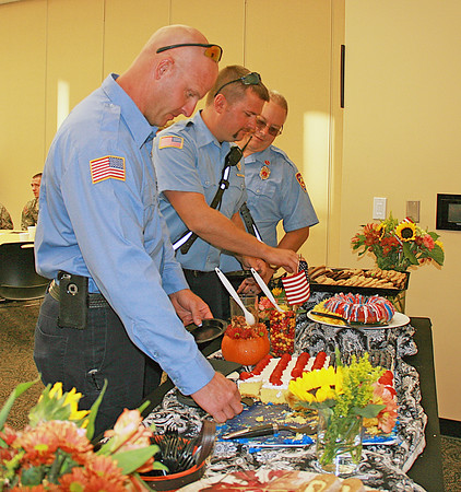 LHS SERVICE APPRECIATION NIGHT<br /> Elizabeth Pearl | The Lebanon Reporter<br /> FIRST RESPONSE: Lebanon Fire Department (from left) Nick Dunn, Brandon Beesley and Lt. Mark Brown grab some snacks at a social hour for veterans and first responders before the Lebanon High School vs. Western Boone Jr.-Sr. High School football game Friday evening. LHS invited all service members to attend the event and game for free.