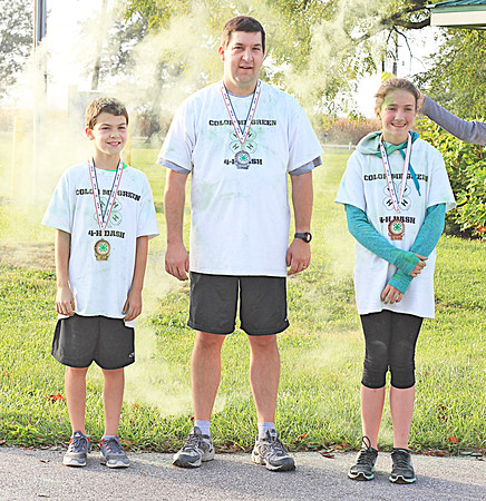 FATHER AND SON TAKE TOP PRIZES IN COLOR RUN<br /> submitted photo<br /> WINNER'S CIRCLE: From left, Boone County 4-H Color Me Green 5K gold medal winner Graham Cavins, 10, Jamestown, silver medalist Jonathon Cavins of Jamestown, and bronze medal winner Molly Barber of Lebanon. Approximately 20 contestants participated in this year's race, and raising about $500 for the Boone County 4-H program.