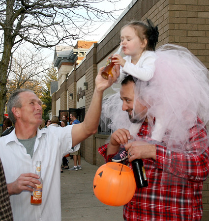 Rod Rose The Lebanon Reporter<br /> YES, THANK YOU; Kairi Paul, 2-1/2, takes a sip of soda offered by her grandfather, Chip Banks, while perched on the shoulders of her father, Bradley Paul, during Saturday's Mischief on Meridian event in downtown Lebanon.