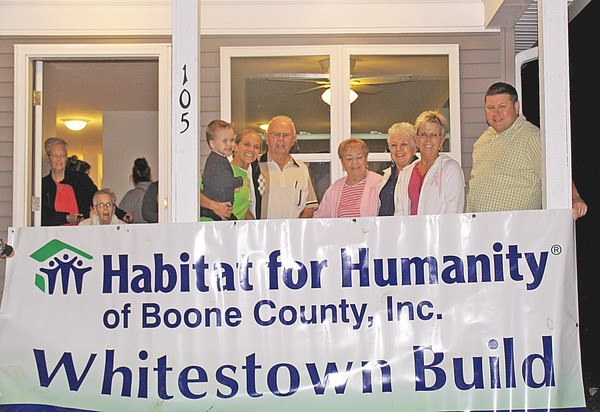 Photo submitted<br /> WELCOME HOME: Juliann Lowe holds her son, Tyler, as she is joined by family and friends on the porch of her Habitat for Humanity of Boone County home in Whitestown.