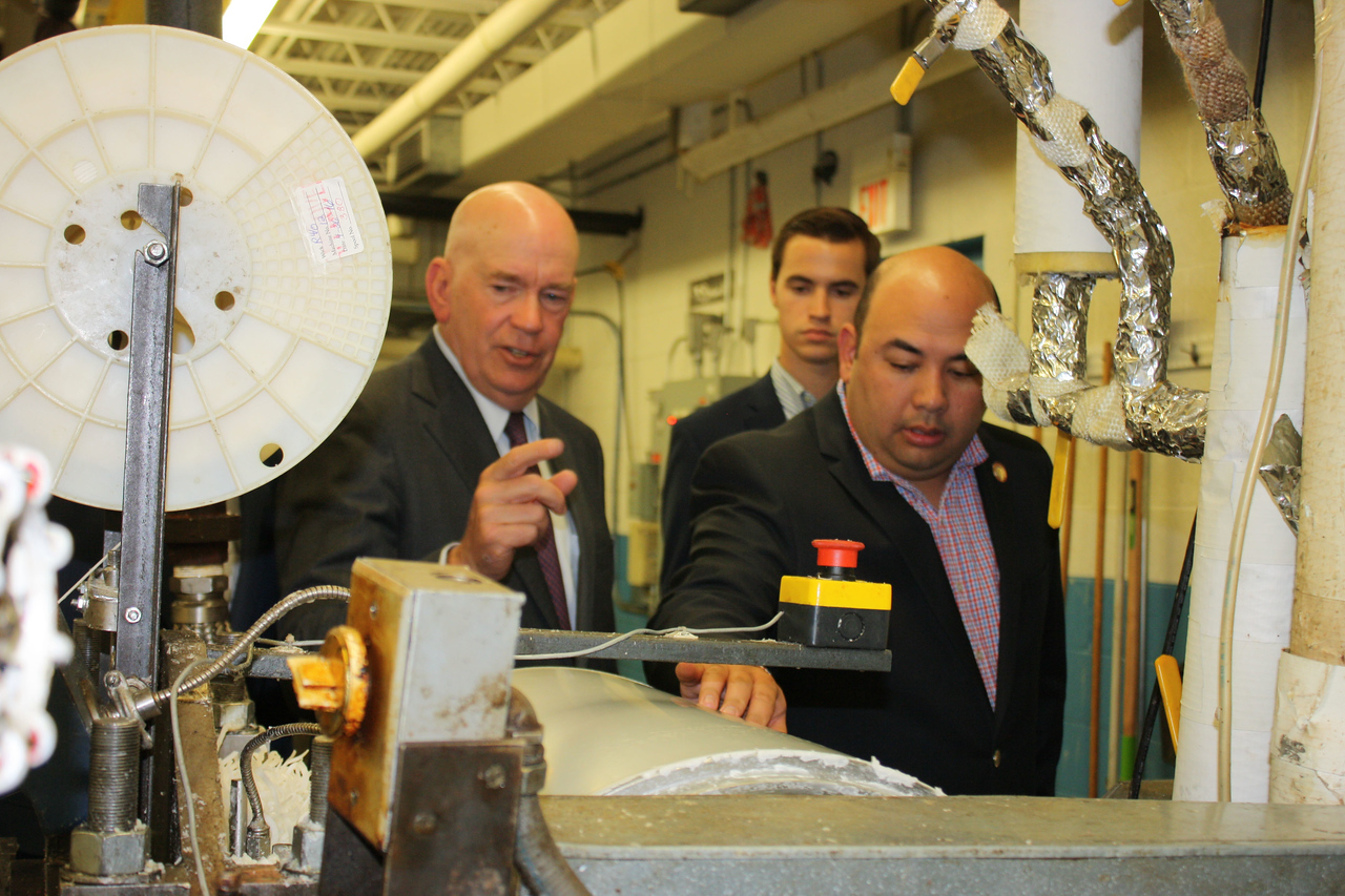 HALEE HEIRONIMUS / GAZETTE Rex Mason, CEO of A.I. Root Candles, shows Speaker Cliff Rosenberger from the Ohio House of Representatives an extruder that makes dinner candles.