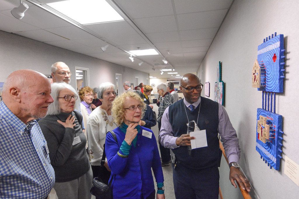. Eric Bonzar �The Morning Journal Eric Gardenhire,right, director of the arts and crafts program at Grafton Correctional Institute and Reintegration Center, talks to residents of Kendal at Oberlin about a piece of art created by inmate Fred Nelson, Feb. 25, 2016. Inmate artwork, spanning numerous mediums, are on display in Kendal\'s Friends Gallery.