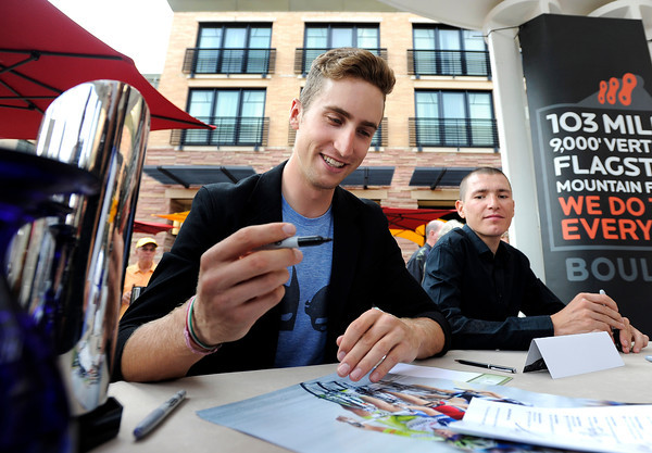 "Olympic cyclist Taylor Phinney, left, laughs as he autographs a poster for a fan on Thursday, Aug. 16, at the St. Julien Hotel and Spa in Boulder. For more photos and video of the event go to  <a href=""http://www.dailycamera.com"">http://www.dailycamera.com</a><br /> Jeremy Papasso/ Camera"