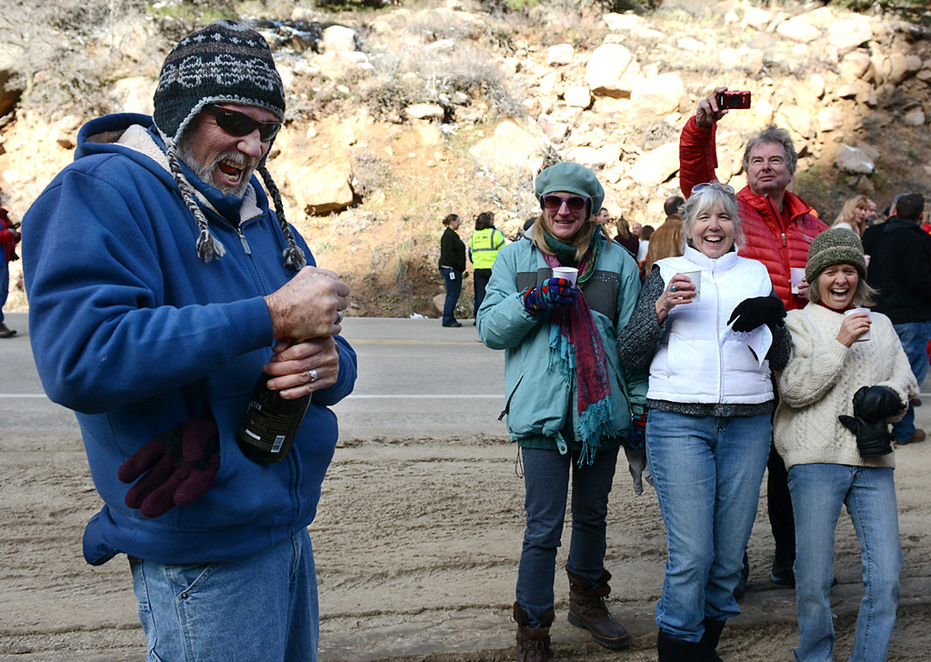 . From left: Mike Dowell struggles to open a bottle of champagne as fellow Allenspark residents Christine Futro, Sharon Arms, Andrew Griffiths, and Peggy Donahue, look on. The group was celebrating the reopening of Colo. Highway 7, between Lyons and Allenspark, Tuesday morning, Nov. 26, 2013. (Lewis Geyer/Times-Call)