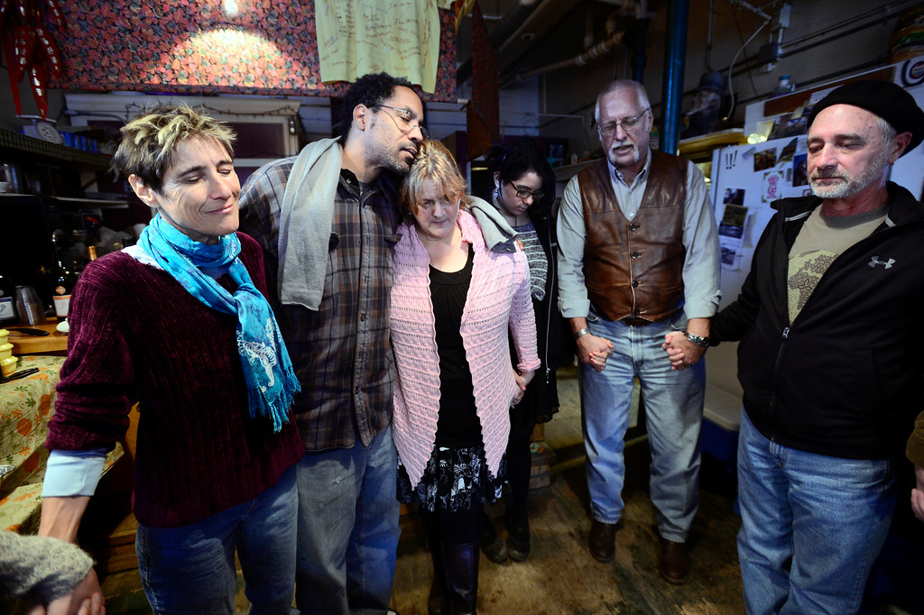 . From left to right Oak Chezar, Perryn, Connie and Maighdeline Gordon, Pastor Paul Rodie and John Greskamp bow their heads as Rodie led a prayer before a Thanksgiving Day dinner at the Jamestown Mercantile for the town that was hard hit by the recent flood.  Thursday November 28, 2013.  Paul Aiken/ Camera