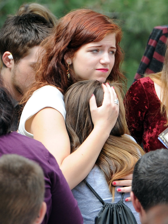 . Emily Briggs, left, comforts a young girl after the memorial service. A memorial service for Wiyanna Nelson and Wesley Quinlan was held at NCAR on Saturday. The teenagers were killed in the flood waters in Boulder.  Cliff Grassmick  / September 21, 2013
