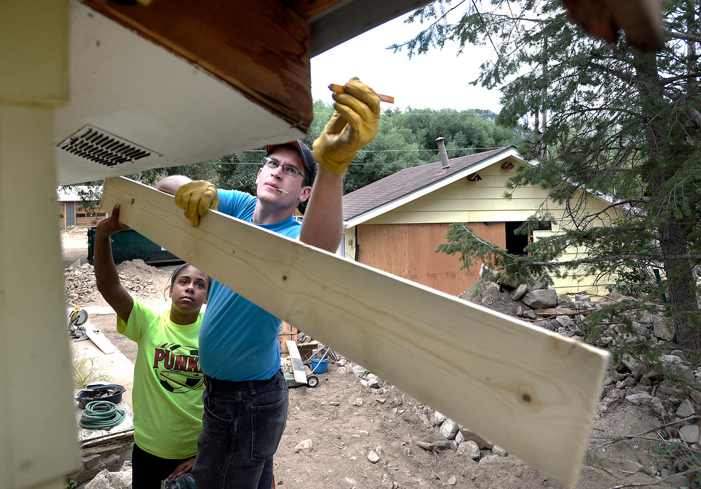 . Lieacha Cook and Will Weeks, of the Mennonite Disaster Service in Hays, Kan., work to repair a soffit on a flood damaged home on Main Street on Friday, July 25, in Jamestown.  Jeremy Papasso/ Camera