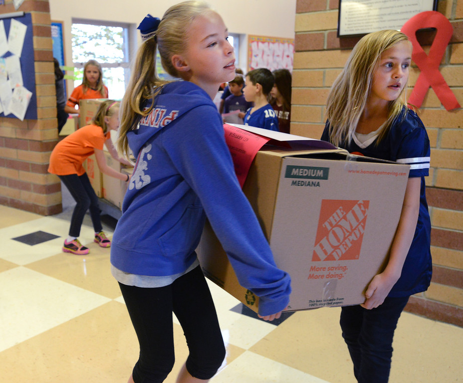 . Coyote Ridge Elementary School fifth graders Ella Mahaffie, left, and Bailee Sheehan , on Friday, carry boxes full of classroom items for Crest View Elementary School in Boulder which suffered flood damage. October 25, 2013 staff photo/ David R. Jennings