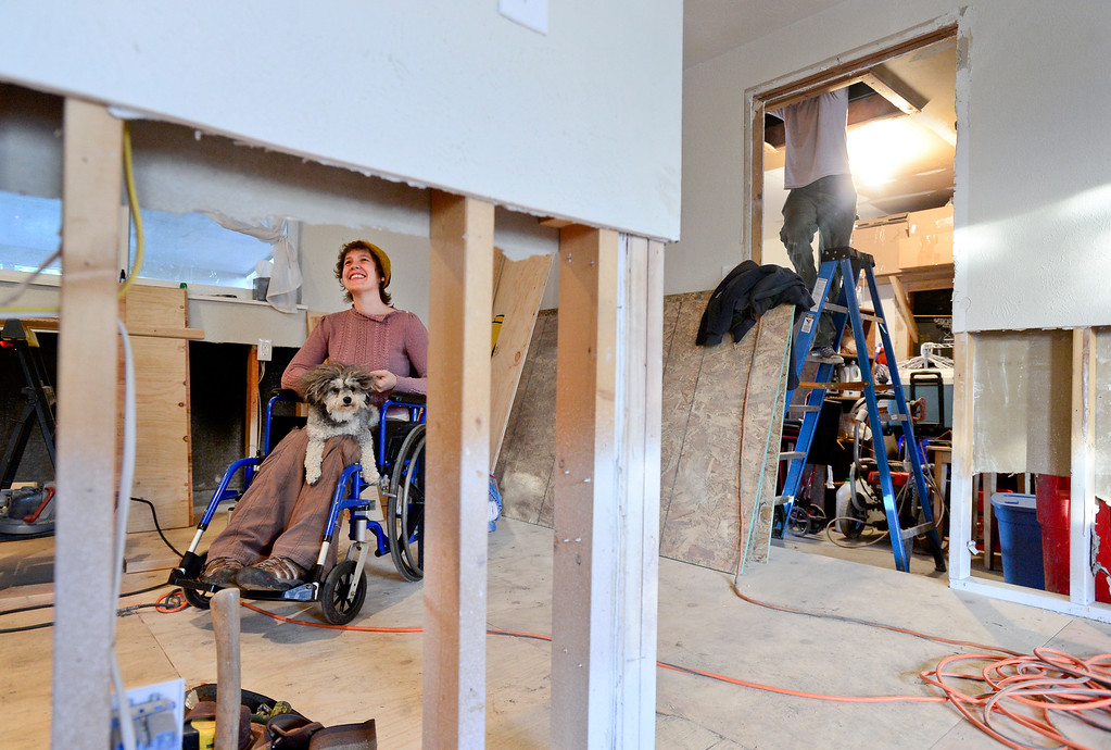 . Rebekah Steers is seen through the exposed studs as her husband Graham Steers climbs into the attic following a structural engineer, Wednesday, Oct. 9, 2013, at their home in Longmont\'s Bohn Park neighborhood. (Matthew Jonas/Times-Call)