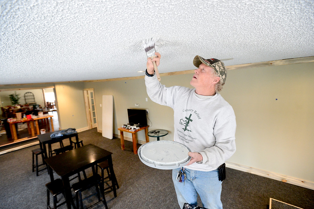 . Volunteer Alan Mackay, of Parker, paints around a smoke detector, Tuesday, April 1, 2014, at the River Community Church in Lyons. (Matthew Jonas/Longmont Times-Call)