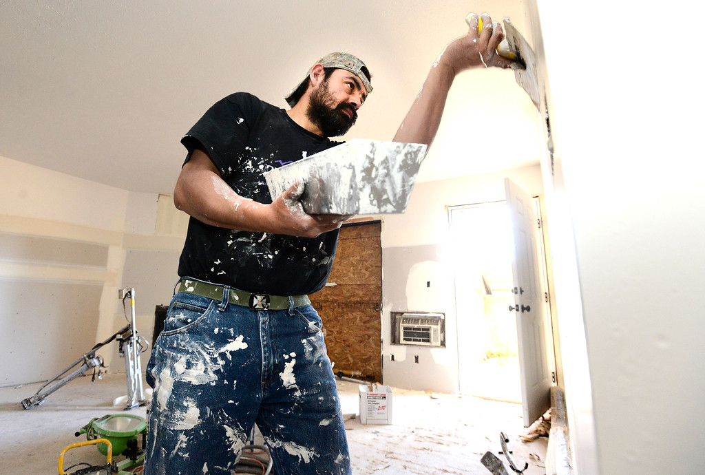 . Luiz Munoz of Charter Drywall works on an apartment on Manhattan Drive in Boulder on Friday. Multiple garden level apartments in the complex were damaged in the September flood. Friday November 29, 2013.  Paul Aiken/ Camera