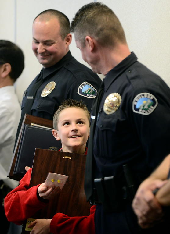 . Joey Gallerani, 9, holds his dad\'s award as both Boulder Police Officer Vinnie Galleriani, right, and Officer Michael Heath, left, were given the Award For Excellence for their actions during the floods of September during a ceremony at the Public Safety Building on Monday. The two officers, while on flood damage assessment patrol, saw military aircraft landing at the Boulder Airport and of their own volition assisted the Boulder County Sheriff\'s Department with the air flood rescue operations starting on September 13, 2013. Photo by Paul Aiken / The Boulder Daily Camera / March 10, 2014