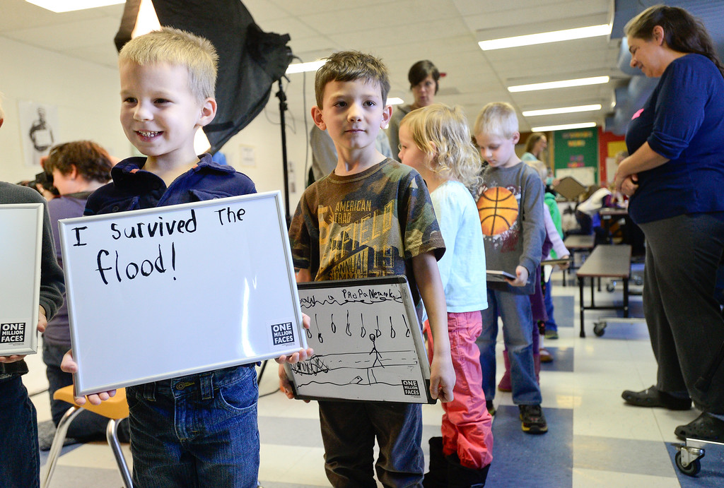 """. Kindergartner Noah Dunn holds a sign reading \""""I survived the flood!\"""" while waiting to have his photo taken by Artist in Residence Peggy Dyer for the One Million Faces project, Monday, Dec. 2, at Lyons Elementary School. (Matthew Jonas/Times-Call)"""