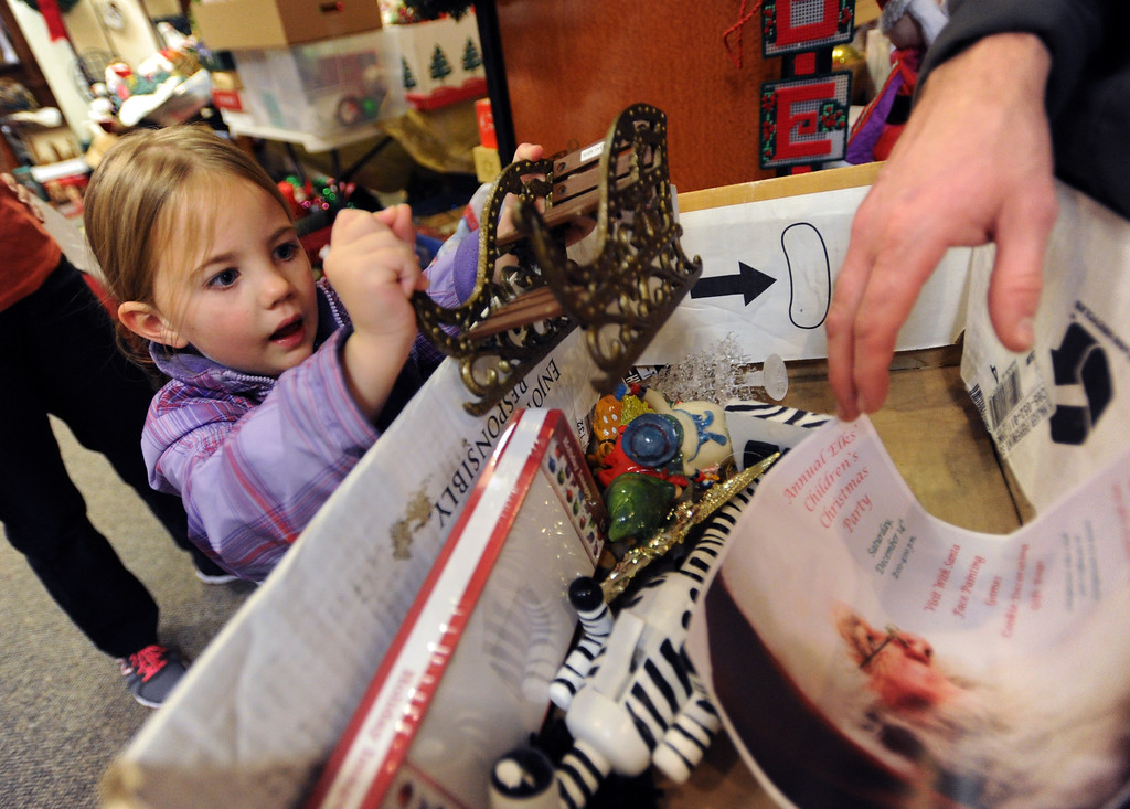 . Ivy Hodge, 3, and her father, Nathan, find Christmas decorations they like on Saturday. Lisa Truesdale has collected Christmas donations and is handing them out to flood victims at the Twin Peaks on Saturday and Sunday from 12-4.  Cliff Grassmick/ November 23, 2013