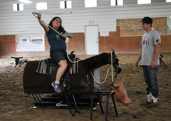 HALEY WARD | THE GOSHEN NEWS <br /> Isis Perez swings a lasso as Loveway volunteer Michael Pippenger looks on during ADEC's summer camp on Friday at Loveway, Inc. Loveway provides people with special needs equine therapy.