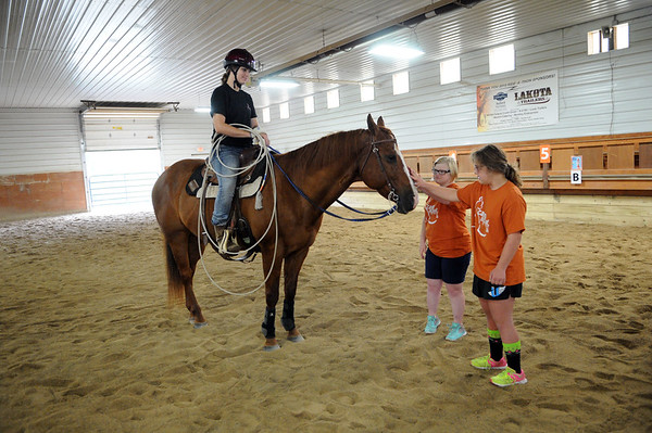 HALEY WARD | THE GOSHEN NEWS <br /> Ellie Wenger and Lexi Tucker pet a horse, Ross, ridden by instructor Maggie Korenstra<br /> during ADEC's summer camp on Friday at Loveway, Inc. The summer camp, which has about 40 campers, attends field trips every Friday. They have been to the petting zoo