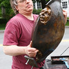 """Andrew DeVries lifts one of his bronze sculptures, """"Chariot"""", from the back of his truck.  The work was installed in front of the Lenox Library along with 24 others around downtown as part of the 10th annual Lenox Art Walk.  Lenox, 5/27/10 - Ian Grey"""