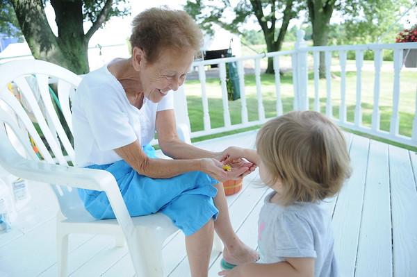 HALEY WARD | THE GOSHEN NEWS<br /> Hazel Eash, 18 months, gives her grandma Kathy a flower Thursday at their Middlebury farm.