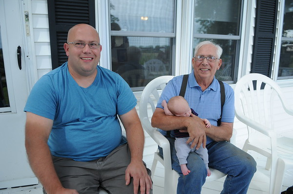 HALEY WARD | THE GOSHEN NEWS<br /> James, 5-weeks-old Corbin and Ray Eash, three generations of farmers, sit on their front porch of the Middlebury farm. They were named Farm Family of the Year by the Ag Society.