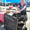 Kate Van Olst from North Plaw Farm cracks an egg into a pan on the grill at the Fenn Street Farmers Market this Saturday August 10, 2013 in Pittsfield. Photos by Sarah Howard/ Special to The Eagle