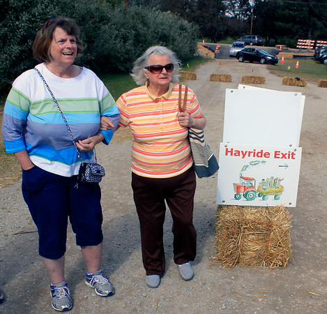 Roger Schneider | The Goshen News<br /> Elizabeth Szymczak of Joliett, Ill. and her daughter, left, Cherie Gimbel of Shorewood, Ill., wait Saturday for a hayride wagon at Kercher's Sunrise Orchard and Farm Market.