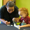 JAY YOUNG | THE GOSHEN NEWS<br /> Shawna Gipson uses a toy dinosaur to knock down a row of dominoes with her son, KJ, as the two play during an open house at the club Saturday morning.