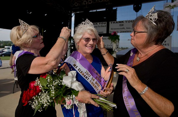 JAY YOUNG | THE GOSHEN NEWS<br /> 2013 senior queen Carole Miller, left, of Goshen, and 2011 senior queen Marcia Krebs, right, of Nappanee, help newly crowned 2017 senior queen Tena Jakubowicz, of Middlebury, with her crown and sash before having photographs taken Friday afternoon.