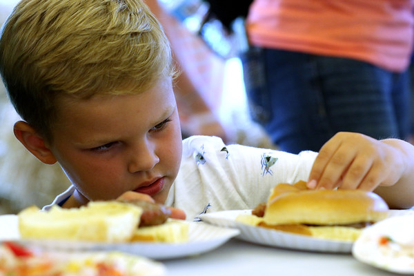 JAY YOUNG | THE GOSHEN NEWS<br /> Six-year-old Zephyr Losee, of Syracuse, looks unsure as he inspects the salsa topped burger he made during the Farm to Table cooking class for kids at the Elkhart County 4-H Fair Monday morning.